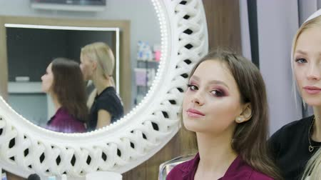 щеткой : Two young, beautiful girls flaunt near the mirror in the beauty salon. Close-up portrait of make-up artist and model who makes evening makeup in front of the mirror. Beautiful young girls in beauty salon