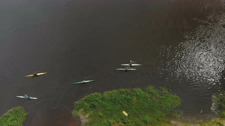 Aerial view drone shot of five people traveling down the river by kayak and canoe. People swim in the water along the shore against the current. Rafting high angle