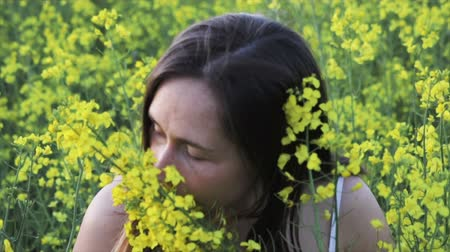 A beautiful carefree girl with healthy hair and freckles on her face against a yellow rapeseed field. Attractive brunette in white dress enjoys and sniffs yellow rape flowers, natural beauty Stock Footage