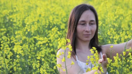 A beautiful carefree girl with healthy hair and freckles on her face against a yellow rapeseed field. Attractive brunette in white dress enjoys yellow rape flowers, natural beauty.