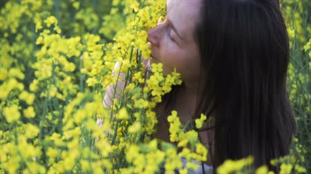 A young girl with dark hair and freckles on her face and a white dress sniffing yellow flowers, she closed her eyes with pleasure. The concept of reunion with nature