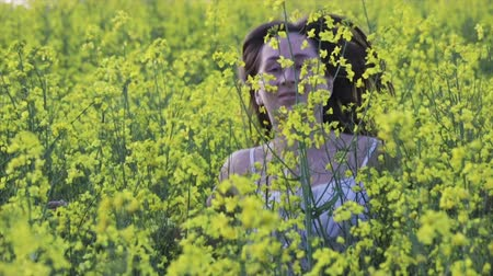 maravilhoso : Sexy young girl in short white dress runs in a field with yellow rape flowers, her dark hair flying in the wind, slow motion