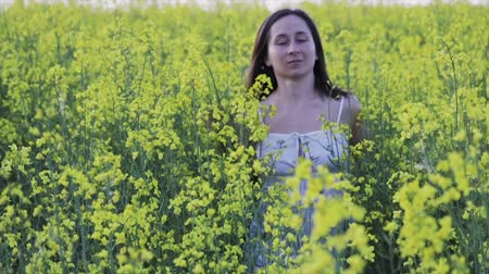 Sexy young girl in short white dress runs in a field with yellow rape flowers, her dark hair flying in the wind, slow motion