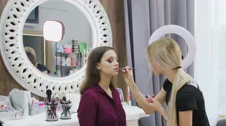 Makeup artist doing makeup for my models brunettes in the beauty salon, the girls behind a large white mirror. Beautiful interior in the cabin Stock Footage