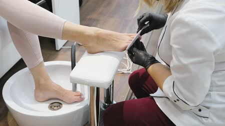 A specialist in a beauty salon makes a French pedicure for the client. Rest in the beauty salon, nail care.