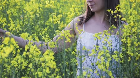 A beautiful woman with dark hair and pigmentation on her face walks in a large rapeseed field in the summer. Girl enjoying nature