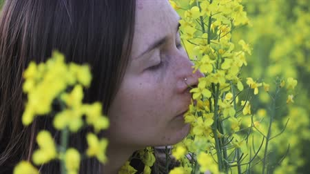 szag : A young girl with dark hair and freckles on her face and a white dress sniffing yellow flowers, she closed her eyes with pleasure. The concept of reunion with nature