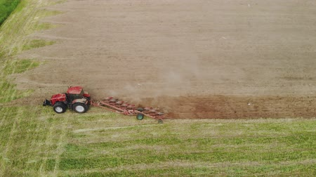 földműves : Top view of the tractor with working plow from the drone pov, agricultural machine red color works the soil for planting Stock mozgókép