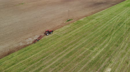 Top view of the tractor with working plow from the drone pov, agricultural machine red color works the soil for planting Stock Footage