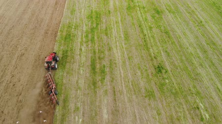 rolník : Top view of the tractor with working plow from the drone pov, agricultural machine red color works the soil for planting Dostupné videozáznamy