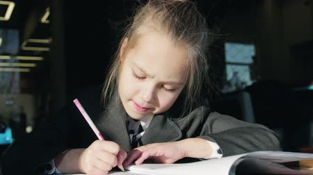 небольшой : Portrait of a small, beautiful schoolgirl who does homework. Girl doing a test in elementary school, writing in pencil in a notebook. Education and training of children