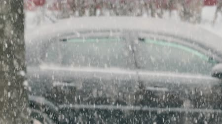 finland : View from the window of the heavy snowfall with lots of wet flakes on the background of the car black. Bad weather conditions in winter