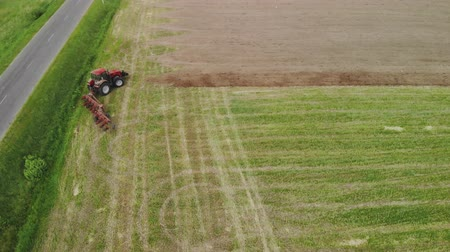 リファレンス : Aerial view power tractor red with working plow on the support wheels is set near an asphalt road and makes plowing the soil for sowing of agricultural crops