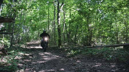enduro : Slow-motion shot of a man in protective gear with a helmet riding an extreme black Enduro on a forest trail among trees and branches with leaves. The art of owning a motorcycle on rough terrain Stock Footage