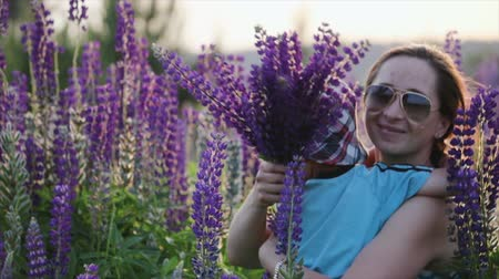 buquê : Mother in dark sunglasses hugs a cute little boy, a son in a blue t-shirt and patterned hat in a field, against a background of narrow-leaved purple lupine flowers. The concept of motherhood, adoption Vídeos
