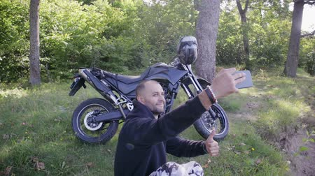 bikers : Young man fotografiruet himself against his motorcycle in a picturesque location, in the fresh air. Motorcyclist takes a selfie on a cliff Stock Footage