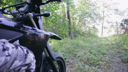 бросаясь : POV slow-motion shot of the riders hand and part of motards black motorcycle, Enduro racing through the woods during the race. Extreme entertainment on rough terrain. The concept of active recreation