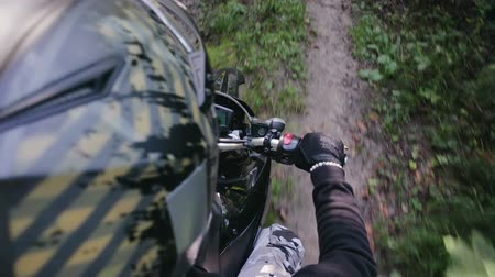 enduro : POV slow-motion shot of a rider in a crash helmet and part of a black motard motorcycle, Enduro racing through the woods during the race. Extreme entertainment on rough terrain. The concept of active recreation Stock Footage