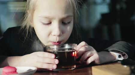 kupa : A beautiful, blond schoolgirl enjoys tea before school. The tea is hot and she blows on it. An inspiring drink that helps you relax and recharge your batteries.