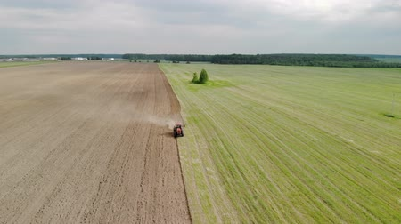 収穫 : Spring farming, aerial view from the drone. Tractor with a plow plows the soil and sows it. Beautiful landscape from above, brown-green land. Agricultural work, soil preparation 動画素材