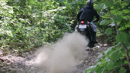 motocros : Athlete in protective gear on a motorcycle Enduro starts, dust and dirt fly from under the wheels. Race in the green forest over rough terrain. The concept of active recreation.