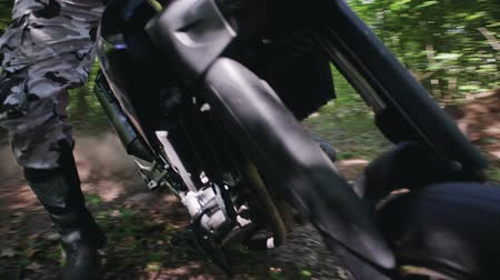 wyscigi : Steadicam shot of a motorcyclist in protective gear and boots performing a drift around its axis on Enduro, motard in a clearing in a dense summer forest