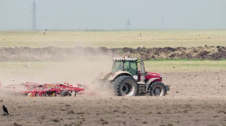 rolník : Side view of red power tractors with multi-functional unit performing the plowing, cultivating and compacting the earth. Dusty agricultural work with soil erosion. Sowing campaign