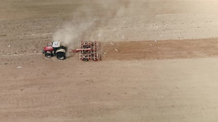 rolník : Side view of red top-high power tractors working the land multifunctional soil cultivating unit for sowing. For dusty agricultural machine flies a lot of white birds. The concept of soil erosion
