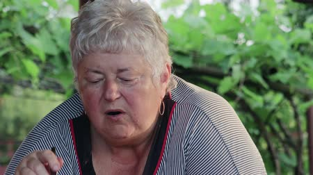 mókás : Funny short-haired elderly overweight woman is eating an outdoor vegetable salad with a spoon and has a pensive look. The lady is missing a front tooth. Healthy lifestyle concept