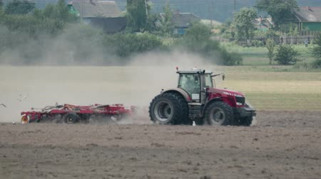 fertility : Side view of red power tractors with multi-functional unit performing the plowing, cultivating and compacting the earth. Dusty agricultural work with soil erosion. Sowing campaign