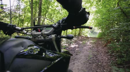 wyscigi : POV slow-motion shot of the riders hand and part of motards black motorcycle, Enduro racing through the woods during the race. Extreme entertainment on rough terrain. The concept of active recreation