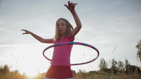 balanço : A little girl in pink clothes learns to cope with the hula Hoop in the fresh air. The kid tries to twist the Hoop around his waist. The child fools around and makes faces, slow-motion effect
