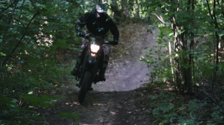 enduro : Motorcyclist in protective gear on black Enduro, motard, extreme riding with dust from under the rear wheel in the dense forest among the trees Sunny weather. The concept of active recreation