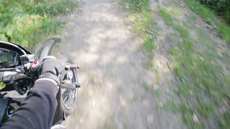 wyscigi : POV slow-motion shot of a rider in a crash helmet and part of a black motard motorcycle, Enduro racing through the woods during the race. Extreme entertainment on rough terrain. The concept of active recreation Wideo