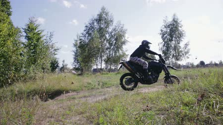 borowina : Side view of a motorcyclist on an off-road motorcycle jumping out of the woods on a natural springboard in Sunny weather. The concept of extreme entertainment and outdoor activities Wideo