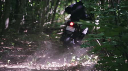 mistrovství : Motorcyclist in protective gear on black Enduro, motard, extreme riding with dust from under the rear wheel in the dense forest among the trees Sunny weather. The concept of active recreation
