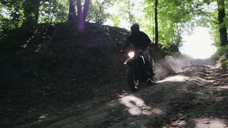 gears : Motorcyclist on a black sports off-road motorcycle famously descends the hill and sweeps past with clouds of sand and dry leaves from under the wheels. Slow motion