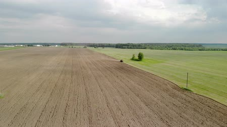solo : Spring farming, aerial view from the drone. Tractor with a plow plows the soil and sows it. Beautiful landscape from above, brown-green land. Agricultural work, soil preparation Stock Footage