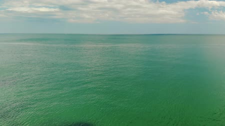 transparente : Aerial view of green-blue sea water surface. The ocean with an endless horizon, merging with cloudy skies Stock Footage