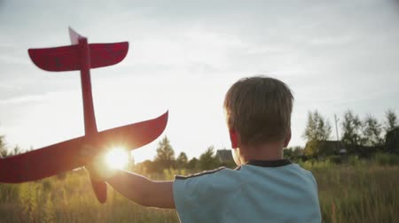 zabawka : Hand-held shot of a young boy 3-5 years old running across a summer field in the setting sun with a pink toy airplane in his left hand. Rear view, close-up. The concept of childhood