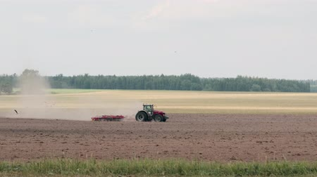 çiftlik hayvan : Tractor processing of the field in the spring, soil preparation by mechanical mixing of different types and layers in the early spring period of agricultural work on the farm. Side view, blurred from the heat Stok Video