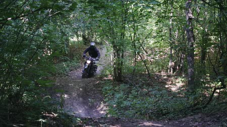 védősisak : Racer in protective gear on a motorcycle SUV rides at high speed through a dense forest with jumps. The concept of motocross