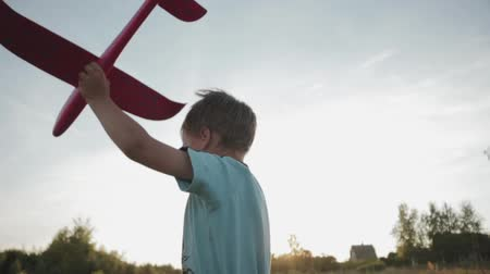 zabawka : Hand-held shot of a young boy 3-5 years old running across a summer field in the setting sun with a pink toy airplane in his left hand. Side view, close-up. The concept of childhood Wideo