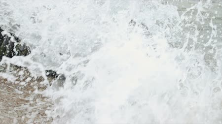 powerful : Slow motion of the sea waves breaking on the rocky ledge of the shore and forming large splashes of water