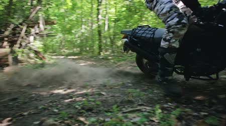 racers : Steadicam filmed a motorcyclist in protective gear and boots performing a drift around its axis on a motorcycle off-road modification in a clearing in a dense summer forest