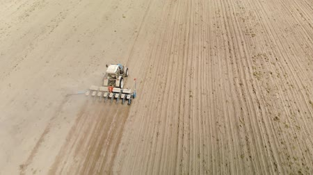 nasiona : Aerial view of a farmer on a blue tractor with a seeder, producing crops on dry dusty soil. The concept of business in agriculture, production of natural products