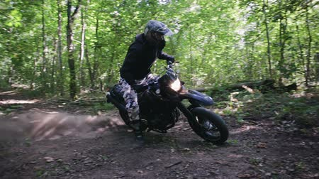 wyscigi : Steadicam filmed a motorcyclist in protective gear and boots performing a drift around its axis on a motorcycle off-road modification in a clearing in a dense summer forest