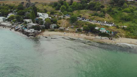 waterkant : Aerial view of the sandy coast with green-blue water and buildings near the beach. Coastline with vacationing tourists. The concept of the resort area on the sea cliff Stockvideo