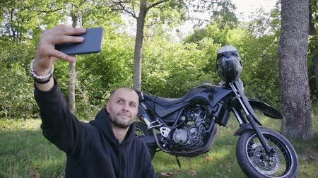 позирует : A handsome, young guy in a dark jacket photographs himself against a black motorcycle in a picturesque place. Selfie style images, motorcycle travel