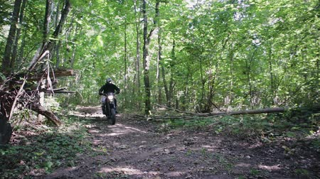 motor vehicle : A Caucasian man in a sports protective suit and helmet rides a black motorcycle over rough terrain with dry autumn leaves. Active lifestyle, travel on Enduro. The road in the forest, dust from under the wheels.